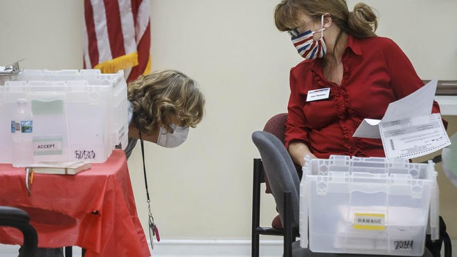 Palm Beach County Supervisor of Elections Office workers sort and review ballots Friday at the supervisor's tabulation center in Riviera Beach.