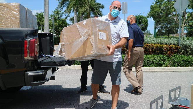 Unity Automotive Group VP of sales Jeff Perusse unloads a box of KN-95 masks the company is donating to Wellington at Village Hall on Thursday. Unity donated 50,000 of the masks to the village.