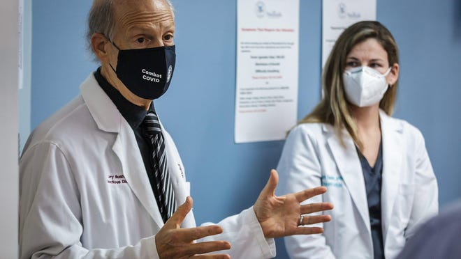 An AstraZeneca COVID-19 vaccine trial is being conducted on the campus of JFK Medical Center in Atlantis, Fla. Dr. Larry Bush and nurse practitioner Elizabeth Sheldon talk to the press on Aug. 17.