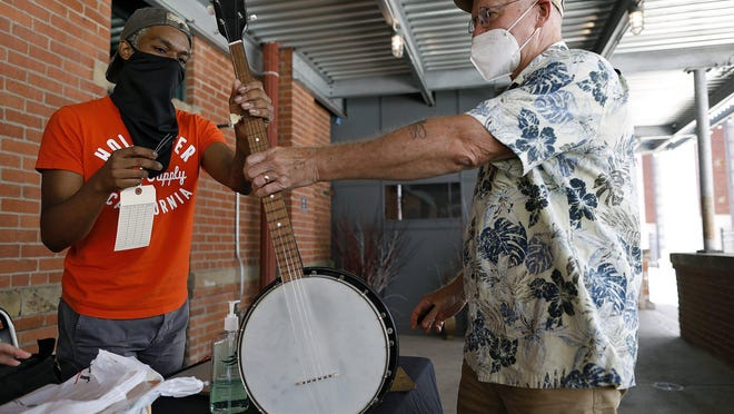 Charles Carter, right, turns in his 50-year-old banjo to Nick Wilson during a Gift of Music campaign drive at Shadowbox Live on Saturday. Gift of Music provides instruments to Columbus City Schools students who can't afford to buy or rent them.
