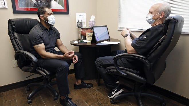 Dee Miller, left, speaks with Dr. Lester Onweller about changing his testosterone regimen at the Low T Center in Dublin. Miller, who was a wide receiver for the Ohio State Buckeyes from 1994 to 1998, is a paid endorser for the clinic.