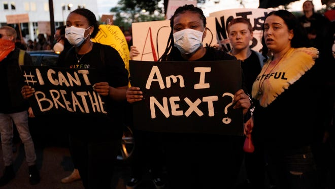 In this May 29, 2020 file photo, women hold up signs during nationwide protests following the death of George Floyd, a black man in Minneapolis who died while in police custody earlier this week.
