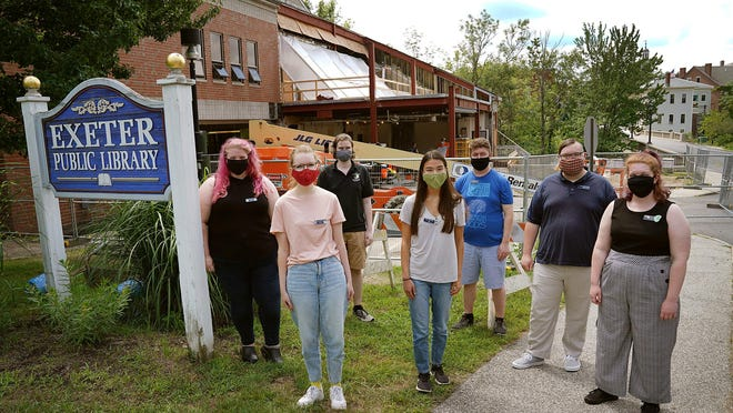 Staff members at the Exeter Public Library gather outdoors in front of construction to renovate and expend the public library this week. From left: Beller-McKenna, Lily Meyers, Rhys Forster, Kelsey Lovejoy, Tyler Boudreau, Will Gleed, and Chandra Boudreau.