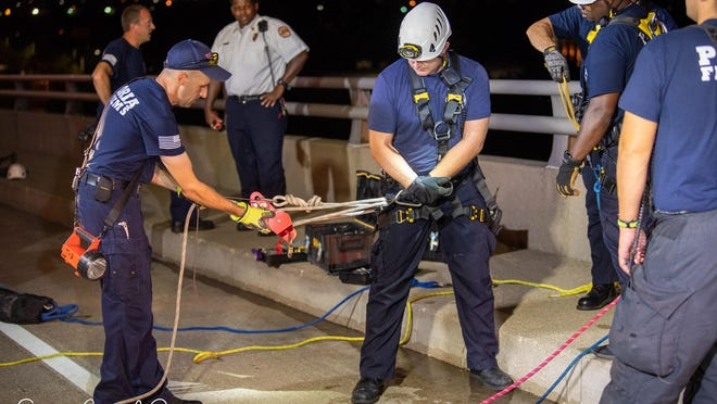 Peoria firefighters prepare to rappel over the side of the Bob Michel Bridge to rescue a man early Saturday, July 25, 2020 who threatened to jump into the Illinois River.