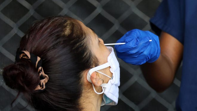 A person gets the swab with the Covid-19 test on her nose during a free test drive on the Good Samaritan Clinic's parking lot on Tuesday, June 23, 2020 in Atlanta, Georgia.