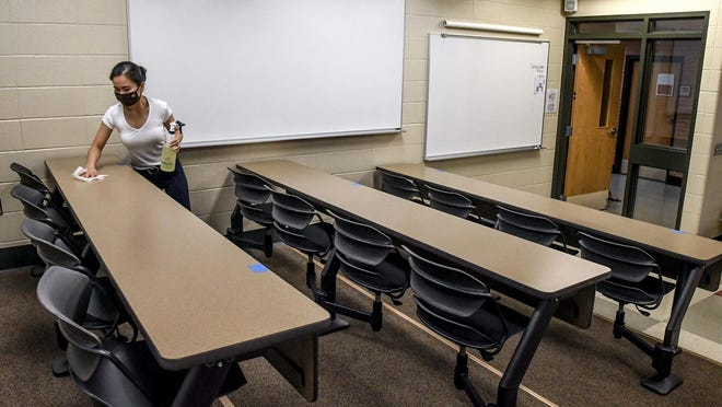 Garden City Community College instructor Thuy Nguyen sanitizes the desks in a classroom after teaching a College Algebra class in it Monday on the first day of the fall semester at GCCC.
