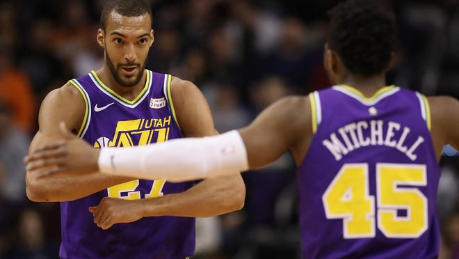 Rudy Gobert (27) of the Utah Jazz is congratulated by Donovan Mitchell (45) after scoring against the Phoenix Suns during the first half on March 13, 2019 at Talking Stick Resort Arena in Phoenix.