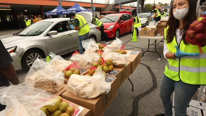 Volunteer Emi Lea Kamemoto, right, moves bags of food to a nearby table as other volunteers load up people's cars with boxes of food in Los Angeles on April 17, 2020.