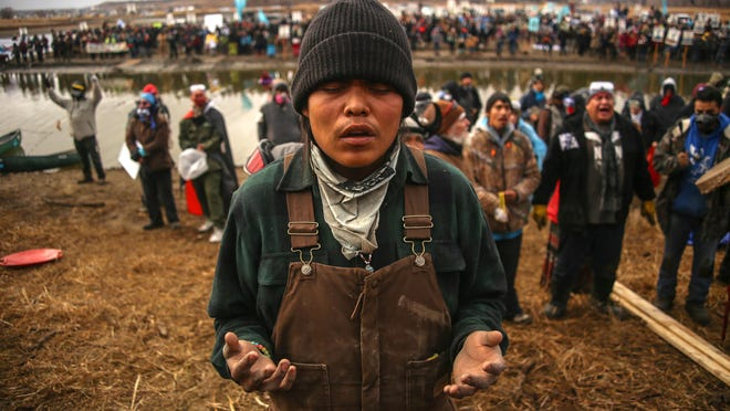 A water protector prays as he and others defend a sacred site near Turtle Island against the Dakota Access Pipeline near the Missouri River at the Standing Rock Indian Reservation.