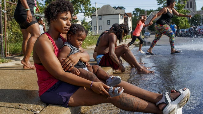 Sabrina Clay holds her 1-year-old nephew while friends and neighbors play in an open fire hydrant in Chicago's Englewood neighborhood on July 26, 2020.