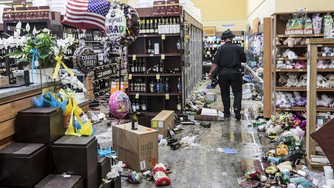 A police officer inspects the damage to a Vons supermarket in Santa Monica, Calif. hours after it was looted on Sunday, May 31, 2020.