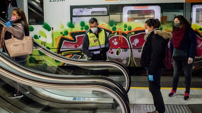 A security guard controls the distance between commuters on escalators at Catalunya station on April 14, 2020, in Barcelona, Spain.