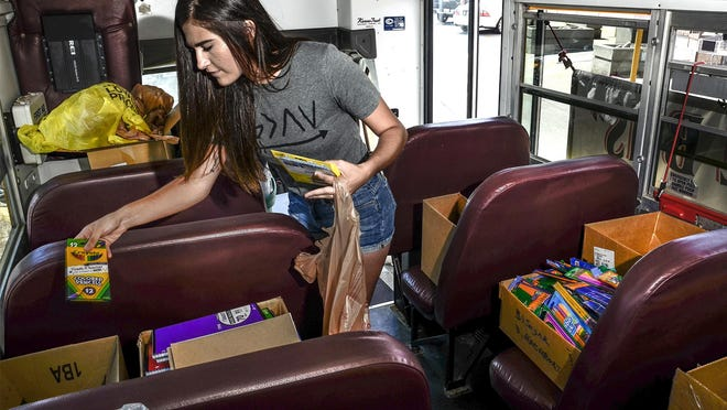 Volunteer Shania Sperry sorts donated school supplies in to the proper boxes in a USD 457 bus during a past Stuff the Bus event. Donation sites will be set up a various locations around Garden City and Holcomb over the weekend for this year's event.