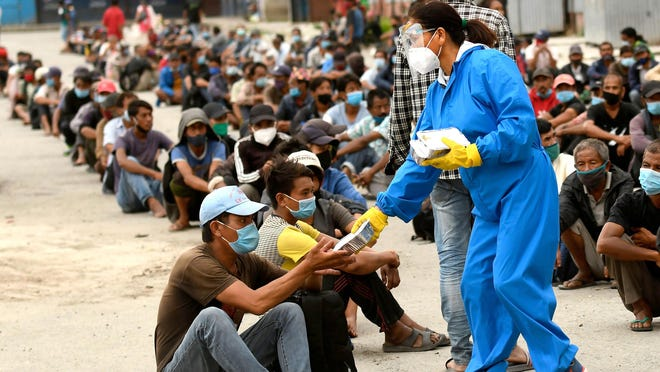 Volunteers distribute food packets people in need after a week-long restrictions were imposed by district officials to contain the spread of the Covid-19 coronavirus, in Kathmandu on Aug. 31, 2020.