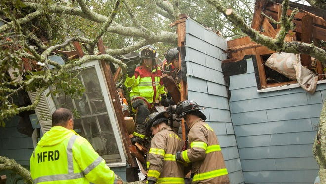 Rescue crews help save Ernestine Law when a tree fell on her house on Wednesday, Sept. 16, 2020 in Mobile, Alabama. Ernestine and her daughter and grandbaby were in the house at the time. The daughter and grandbaby were able to get out, but Ernestine was trapped inside. Hurricane Sally made landfall in Alabama early Wednesday.