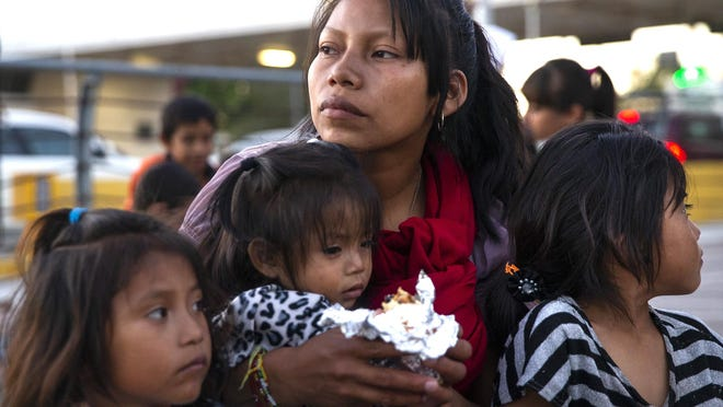 Patricia Giron (center) holds her daughters, Yesenia (left), 6, Wendy (center), 1, and Yocelyn, 6, at the temporary tent camp of asylum-seekers in Matamoros, Mexico, on Dec. 14, 2019. The Giron family, from Chiapas, Mexico, is living in temporary tent shelters under the Migrant Protection Policy, which requires asylum-seekers to wait in Mexico while their asylum claims are processed.