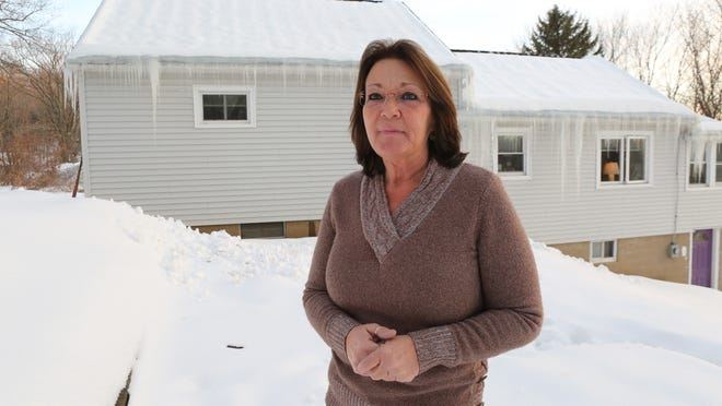 Roseanne Di Guilio stands Feb. 10 in front of her home that straddles the New York and Connecticut state line. She lost half of it in a weird tax foreclosure by Putnam County.
