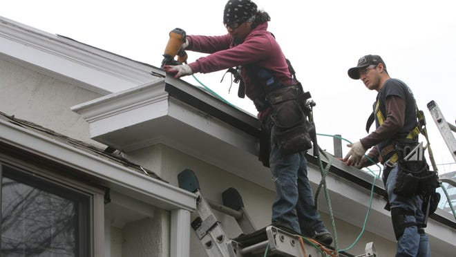 Wearing safety harnesses, workers Marco Ortiz and Israel Hidalgo of Franzoso contracting, work on a roof on April 14, 2015 at an Ossining home that is being re-shingled.