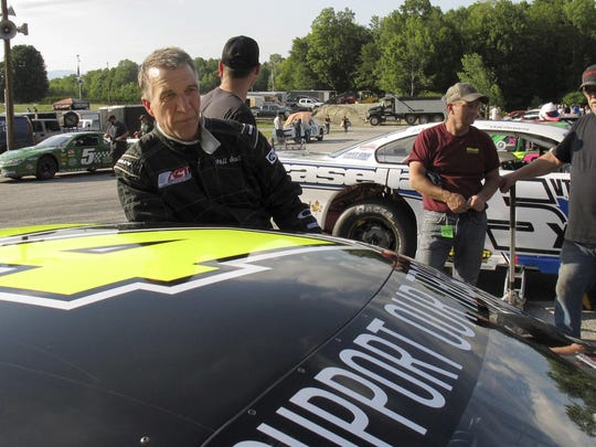 In this file photo, Vermont Gov. Phil Scott stands by his stock car at the Thunder Road race track before winning the evening's 50-lap feature race, his 30th lifetime win.