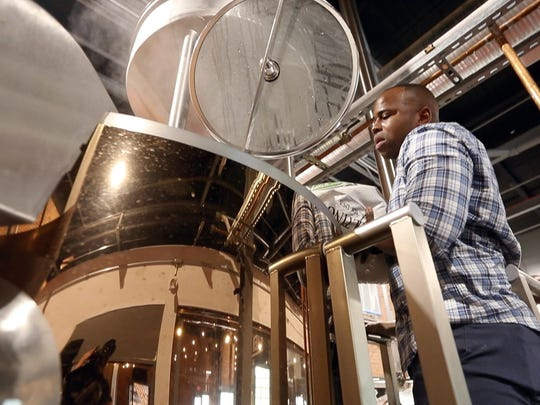 """Peekskill police officer Jonathan Saintiche loads malted barley into a tank as he and other members of the police department assist in brewing a special beer at River Outpost Brewery in Peekskill May 22, 2018. The brewery is partnering with the police department in creating a beer called """"PeaceSkill"""" that will be sold as a fundraiser for the police departments gun buyback program."""