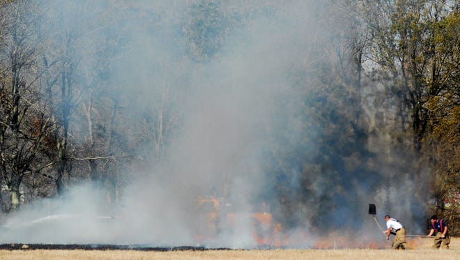 Firefighters work to put out a grass fire.