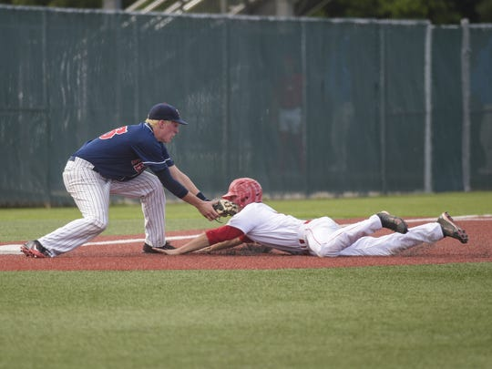Tioga outfielder Cameron Sanders (7) is tagged out on a slide at third base by Teurlings' third baseman Jonathan Fontenot (26) during the third inning of Thursday's 4A semifinal game.