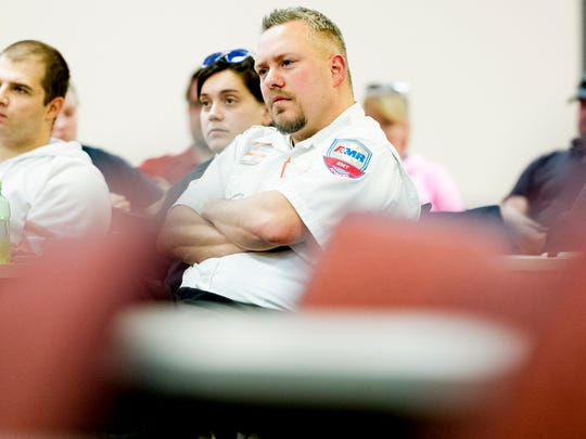 An AMR EMT listens during a ceremony honoring AMR and