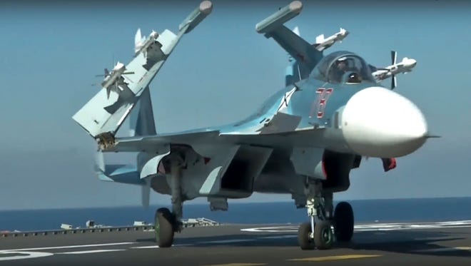 A Russian Su-33 fighter jet stands on the flight deck of the Admiral Kuznetsov aircraft carrier in the eastern Mediterranean Sea.