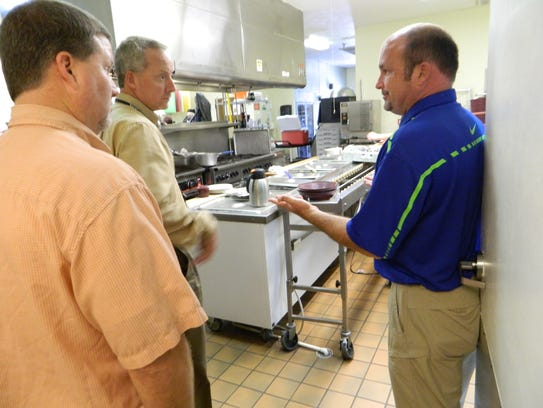 Barry Cotton, right, shows the kitchen area of Signature