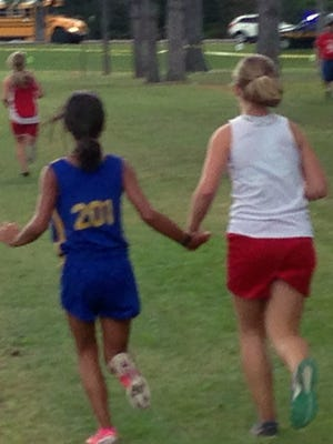 Makenna Finnegan, right, a student at Shelby Middle School in Shelby, Ohio, holds hands with Elaine Hohman of Donnell Middle School in Findlay, Ohio, as the pair finish a cross-country race together Sept. 19, 2015, in Galion, Ohio.