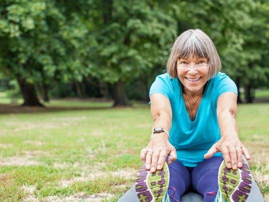 Fit elderly woman exercising in park