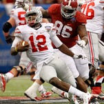 Ohio State quarterback Cardale Jones (12) scrambles away from pressure from Alabama defensive lineman A'Shawn Robinson (86) at the Sugar Bowl.