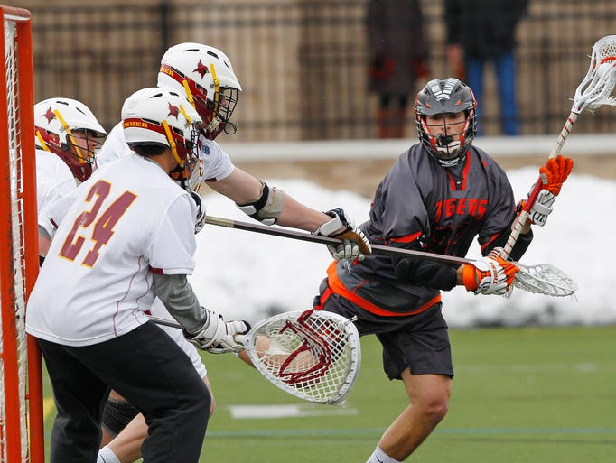 RIT's Eddie Kiesa, right, gets around St. John Fisher's Gregory Bell, top left, before getting a shot past goaltender Jamie Campagna for a Tigers goal.