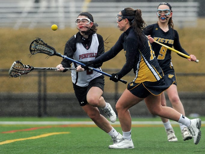 Victor's Allie Rupp, right, knocks the ball away from Penfield's Jamie Forken during a regular season game played at Penfield High School on Monday, April 7, 2014. Penfield beat Victor 13-11.