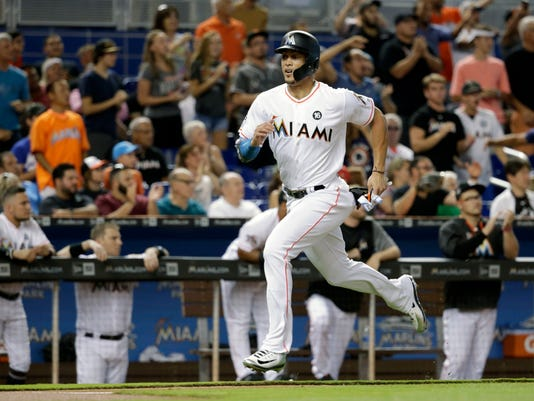 Miami Marlins' Giancarlo Stanton runs home to score on a double hit by Christian Yelich during the first inning of a baseball game against the San Francisco Giants, Tuesday, Aug. 15, 2017, in Miami. (AP Photo/Lynne Sladky)