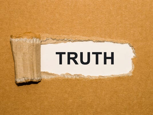 The text Truth appearing behind torn brown paper