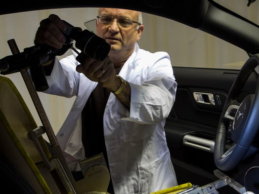 An engineer adjusts an instrument inside a new Ford Mustang