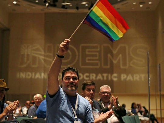 Spectators wave LGBTQ pride flags as Pete Buttigieg, mayor of South Bend, Indiana, addresses the audience during the 2016 Indiana Democratic state convention in Indianapolis  June 18, 2016.