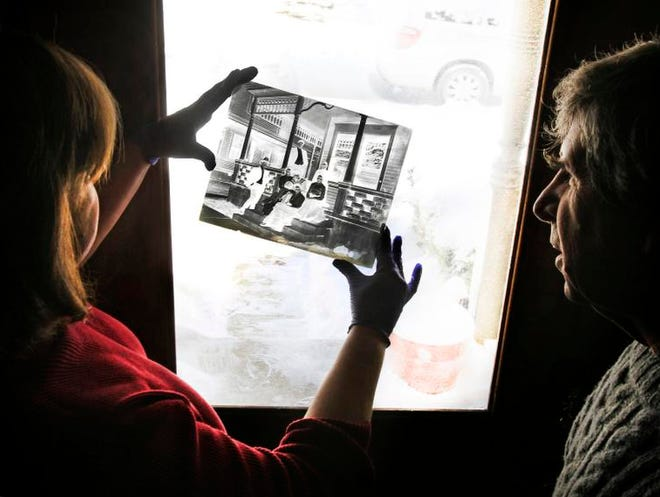 Joan Hostetler (left), who operates Heritage Photo & Research Services, inspects a glass plate negative of a photograph taken in Woodruff Place brought to her Feb. 6, 2014, by Kimball Lloyd-Jones.