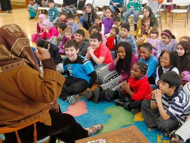 """Children breaks into laughter as Sister Najmah Abdulmateen tells the story """"How Brer Rabbit Outsmarted the Frogs"""" during the Reading Under the Stars event at Westfall Academy on Saturday."""