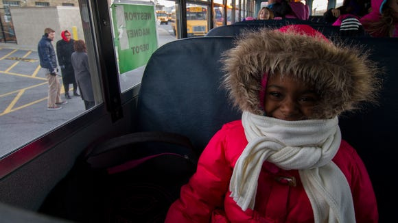 Bundled up Lincoln Elementary Performing Arts School second grader, Khamari Brown, smiles for a portrait  on her bus after the school's dismissal.  January 7, 2015.