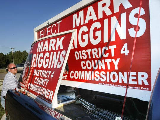 Mark Riggins loads one of his campaign signs from the Thursday's election into his truck on Friday. Riggins is one of four new commissioners who will be serving on the County Commission.