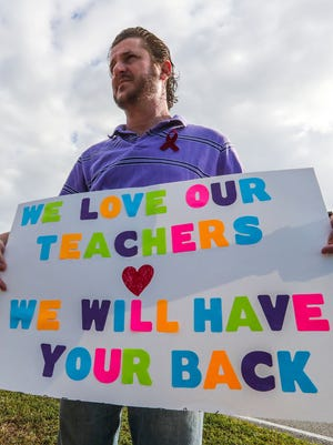 Ian Kravitz, 47, of Parkland, Fla., holds a sign and waves to teachers as they arrived Feb. 26, 2018, at Marjory Stoneman Douglas High School in Parkland. His daughter, Madyson, 17, a junior the school.