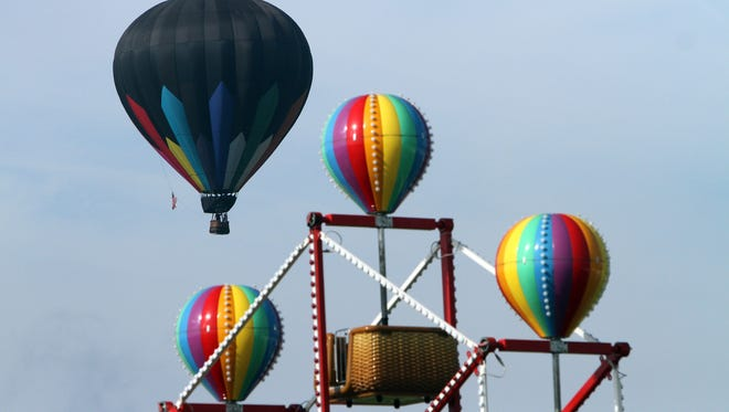 A hot air balloon flies past the Balloon Fiesta arcade ride at the 35th annual QuickChek New Jersey Festival of Ballooning at Solberg Airport in Readington, NJ, the largest summertime hot air balloon and music festival in North America as well as the premiere family entertainment attraction in New Jersey. July 27, 2017. Readington, NJ