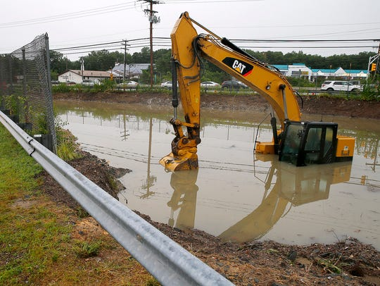 A piece of construction equipment sits in a flooded