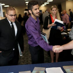 Military veterans listen as a recruiter for Internal Revenue Service explains the jobs available during the Veterans Career and Resource Fair hosted by Florida International University and the Miami Vet Center.