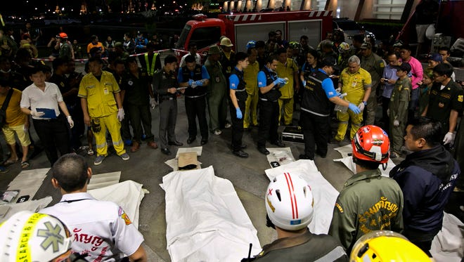 Covered bodies of victims lie next to Thai forensic police officers and rescue workers outside Siam Commercial Bank (SCB) headquarters in Bangkok, Thailand, March  14, 2016.