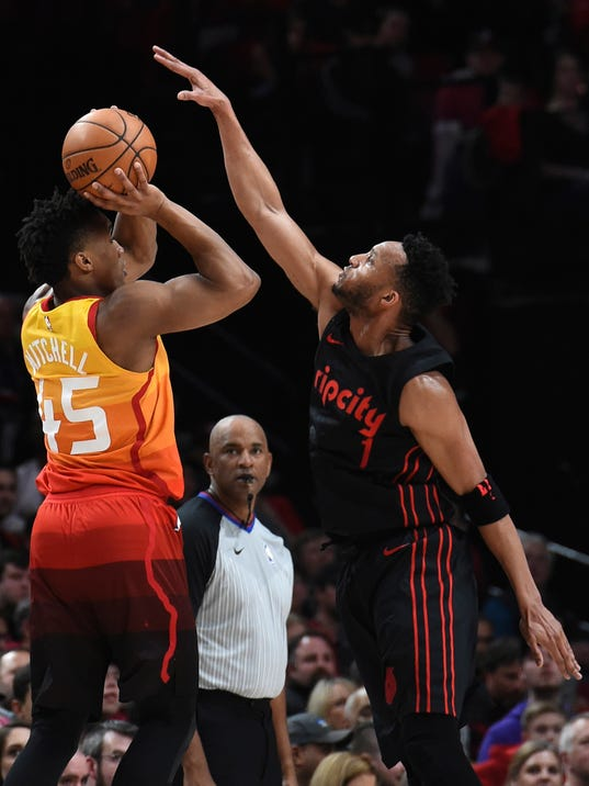 Portland Trail Blazers forward Evan Turner, right, goes up to block the shot of Utah Jazz guard Donovan Mitchell, left, during the first half of an NBA basketball game in Portland, Ore., Wednesday, April 11, 2018. (AP Photo/Steve Dykes)