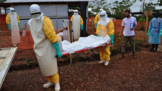 Medicins Sans Frontieres (Doctors Without Borders) medical workers wearing protective clothing carry the body bag of an Ebola victim at the MSF facility in Kailahun, on Aug. 14.