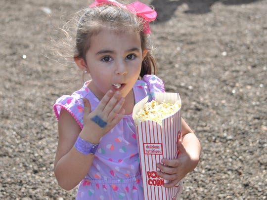 Adelyn Thompson snacks on some popcorn Saturday morning